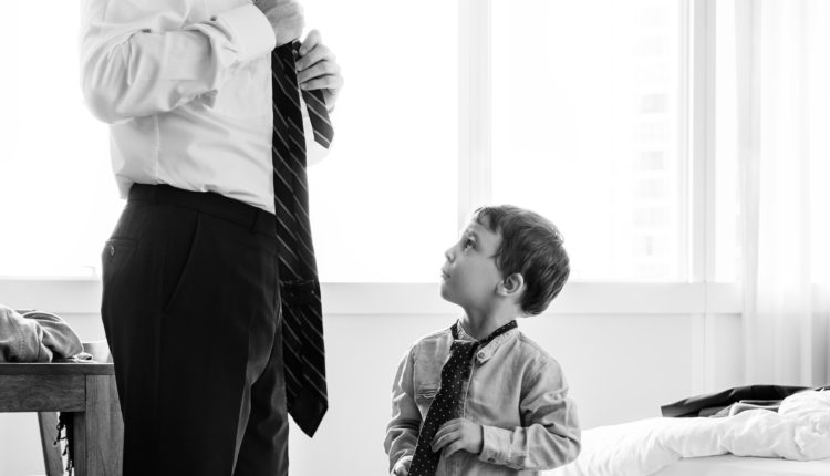 Father teaching son how to tie a tie